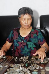 CHINESE WOMAN TROLLS RIVER BANKS FOR OLD COINS